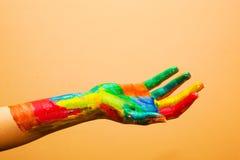 Main peinte, amusement coloré. Fond orange photos stock