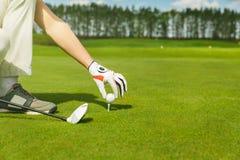 Main plaçant la boule de golf sur la pièce en t photo libre de droits
