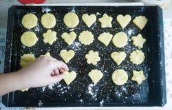 Main plaçant un biscuit en forme de coeur sur un plateau photographie stock libre de droits