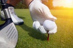 Main plaçant une pièce en t avec la boule de golf Images libres de droits