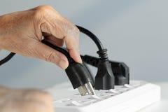 Main pluse âgé branchant au débouché électrique Photos stock