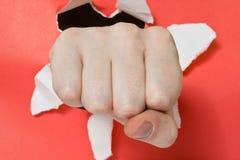 Main poinçonnant par le papier rouge Photo stock