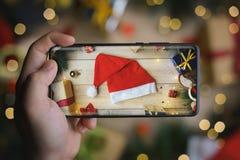 Main prenant la photo de Santa Hat With Infinite Display Smartphon images stock