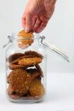 Main prenant le biscuit fait à la maison d'Anzac Photos stock