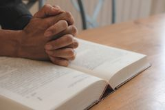 main priant sur la Sainte Bible d'ouverture foi, concept de religion image libre de droits