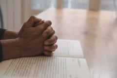main priant sur la Sainte Bible d'ouverture foi, concept de religion images stock
