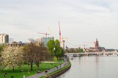 Main promenade in Frankfurt, Holbeinsteg-bridge and Imperial Cathedral in the background. Frankfurt, Germany - April 1st 2014. View of the Main promenade in Royalty Free Stock Photography