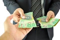 Main recevant l'argent - dollars australiens Photographie stock libre de droits