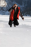 Main in red jumping on winter lake Royalty Free Stock Image