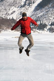 Main in red jumping on winter lake Royalty Free Stock Photos
