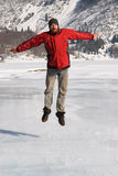 Main in red jumping on winter lake Stock Images