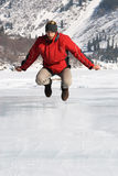 Main in red jumping on winter lake Royalty Free Stock Photo
