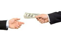 Main remettant l'argent à une autre main Photographie stock
