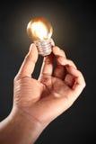 Main retenant l'ampoule Image stock