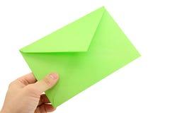 Main retenant l'enveloppe verte Photographie stock libre de droits