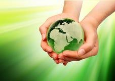Main retenant la terre verte Images libres de droits