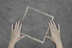 Main retenant la trame en bois sur le mur en béton Photographie stock libre de droits