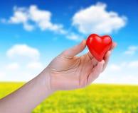 Main retenant le coeur rouge Image stock
