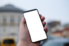 Main retenant le téléphone intelligent mobile avec l'écran blanc photographie stock libre de droits