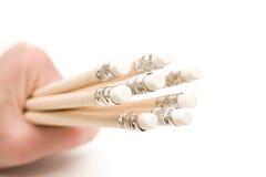 Main retenant les crayons en bois avec des gommes à effacer photographie stock libre de droits