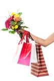 Main retenant les sacs à provisions et les fleurs colorés Photo libre de droits
