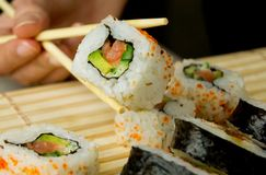 Main retenant les sushi japonais Photos stock