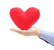Main retenant un oreiller en forme de coeur rouge Images libres de droits