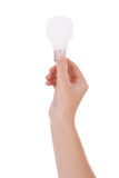 Main retenant une ampoule incandescente Image stock