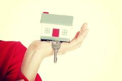 Main retenant une clé de maison Images stock