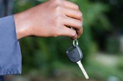 Main retenant une clé de véhicule Photo stock
