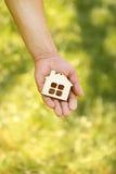 Main retenant une maison en bois Photographie stock libre de droits