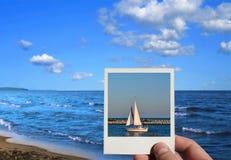 Main retenant une photo de vacances Photo stock