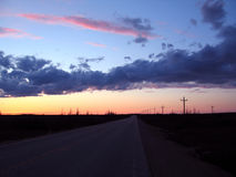 Main Road. Road with beautiful sky formation, land silhouettes stock images