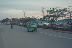Main Road going to Tagum City Bus Terminal. With a green motorcycle in focus which is the primary means of transportation for local within the city proper Royalty Free Stock Photo