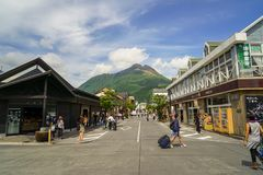 Main road from train station filled with tourists, streetscape and local shops direct to fresh green Yufudake mountain peak and bl Stock Images