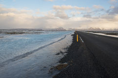 Main road in winter time with blue water on the edges, Iceland Stock Photography