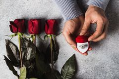 Main romantique d'homme de jour de valentines tenant la bague de fiançailles dans la boîte Photographie stock libre de droits