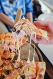 Main sélectionnant la pizza de fromage Photo stock