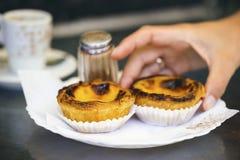 Main saisissant la pâtisserie portugaise typique - le Pastel de nata Photographie stock