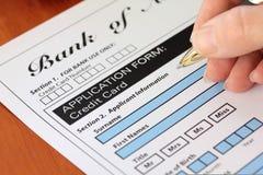 Main signant une application par la carte de crédit factice Photographie stock