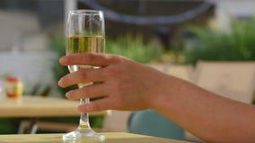 Main soulevant un verre de champagne Bouillonne le plan rapproché 4K banque de vidéos