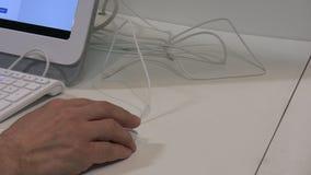 Main, souris, clavier blanc et affichage banque de vidéos