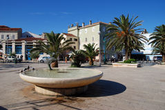 Main square with dolphin fountain in Mali Losinj,Croatia. Dolphin's fountain in Mali Losinj on the main square with houses and palm trees Stock Photo