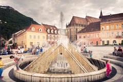 The main square of the medieval city of Brasov, Romania. October 10nd, 2015. Black Church in the middle background and a fountain the foreground Stock Image