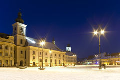 Main square winter snow Sibiu Romania. Main square winter snow historical arhitecture in Sibiu Romania catholical church public lantern and tower in background Royalty Free Stock Photography