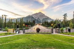 Main street in Banff with Cascade Mountain towering over town, A. Main street in Banff with Cascade Mountain towering over town at sunset, Alberta, Canada stock images