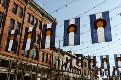 Main street in Denver. Larimer street in Denver with Colorado flags sunny buildings houses hanging bright busy main square downtown dusk daylight metropolitan royalty free stock photography