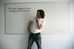 The main subject of the image is not in focus. A man posing as a model with a whiteboard in a funny way Stock Images