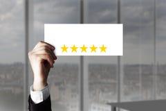 Main supportant petits les étoiles de évaluation du signe cinq Photographie stock libre de droits