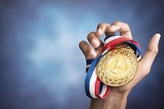 Main supportant une médaille d'or Photographie stock libre de droits